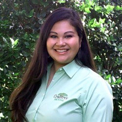 an up close shot of administrative assistant for crabtree dental ashley in front of a bush